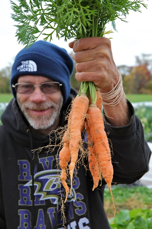 David Ruch posing with Red Wiggler carrots.